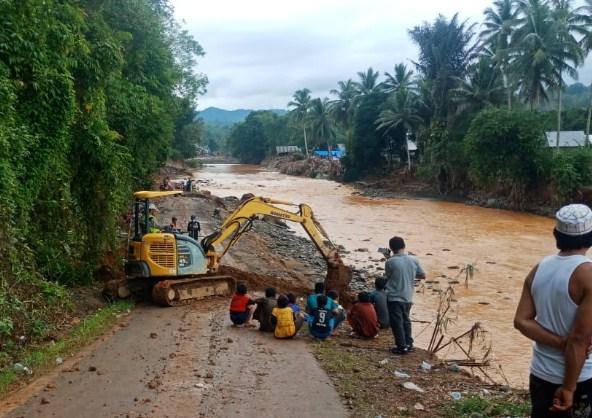Kondisi Jalan di Desa Halat Kecamatan Hantakan, Kabupaten Hulu Sungai Tengah, yang terkena terjangan banjir. Alat Berat Eksavator Mini milik Pemkab Barito Utara, saat menangani pembukaan jalan yang tertutup oleh longsor akibat terjangn banjir.